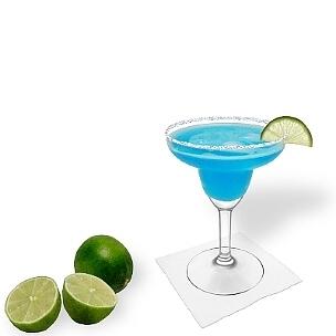 Blue Margarita servido en una copa de margarita con un pedazo de lima y pizca de azúcar o sal, es la manera más común de presentar esta bebida con tequila impresionante y refrescante.